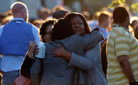 Women embrace while reuniting at a gathering point for family members of Navy Yard employees that was set up inside Nationals Park in the wake of the shooting September 16, 2013 in Washington, DC. Police believe at least one gunman shot and killed at least 12 people and wounded others in an incident that put parts of the city on lockdown. Photo: Win McNamee, Getty Images / 2013 Getty Images