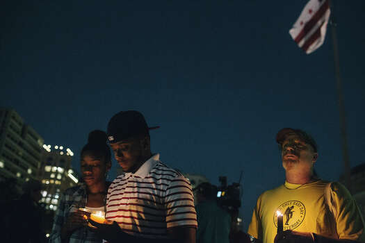 Brittany Carter, of Bowie, MD., (L) Jibri Johnson, of Landon, MD., (C) and Bryan Beard of Washington D.C. hold candles in remembrance of people affected by gun violence during a vigil at Freedom Plaza on September 16, 2013 in Washington, DC.  The vigil, during which organizers called for stricter gun laws, was in remembrance of the 12 victims killed in a shooting at the Washington Navy Yard earlier in the day. Photo: Greg Kahn, Getty Images / 2013 Getty Images