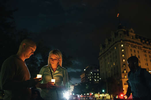 Dave Gray and wife Brittany, of Salt Lake City, hold candles in remembrance of people affected by gun violence during a vigil at Freedom Plaza on September 16, 2013 in Washington, DC.  The vigil, during which organizers called for stricter gun laws, was in remembrance of the 12 victims killed in a shooting at the Washington Navy Yard earlier in the day. Photo: Greg Kahn, Getty Images / 2013 Getty Images