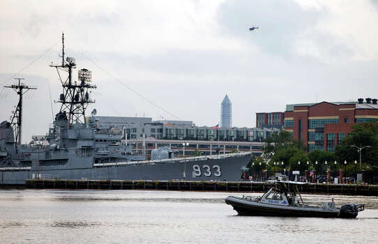 A police boat and helicopter patrol near the scene of a shooting at the Washington Navy Yard on Monday, Sept. 16, 2013, in Washington. At least one gunman opened fire inside a building at the Washington Navy Yard, and officials said six people were killed and as many as 10 were wounded, including a law enforcement officer. Photo: Evan Vucci, ASSOCIATED PRESS / AP2013