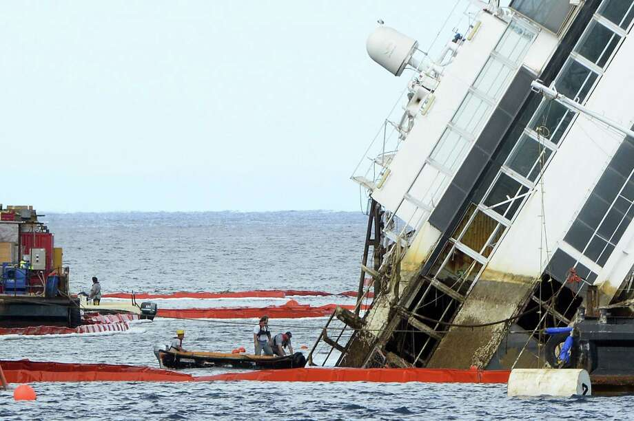 Crews work on the Costa Concordia, which capsized off an Italian island. Thirty-two people died. Photo: Andreas Solaro / AFP / Getty Images