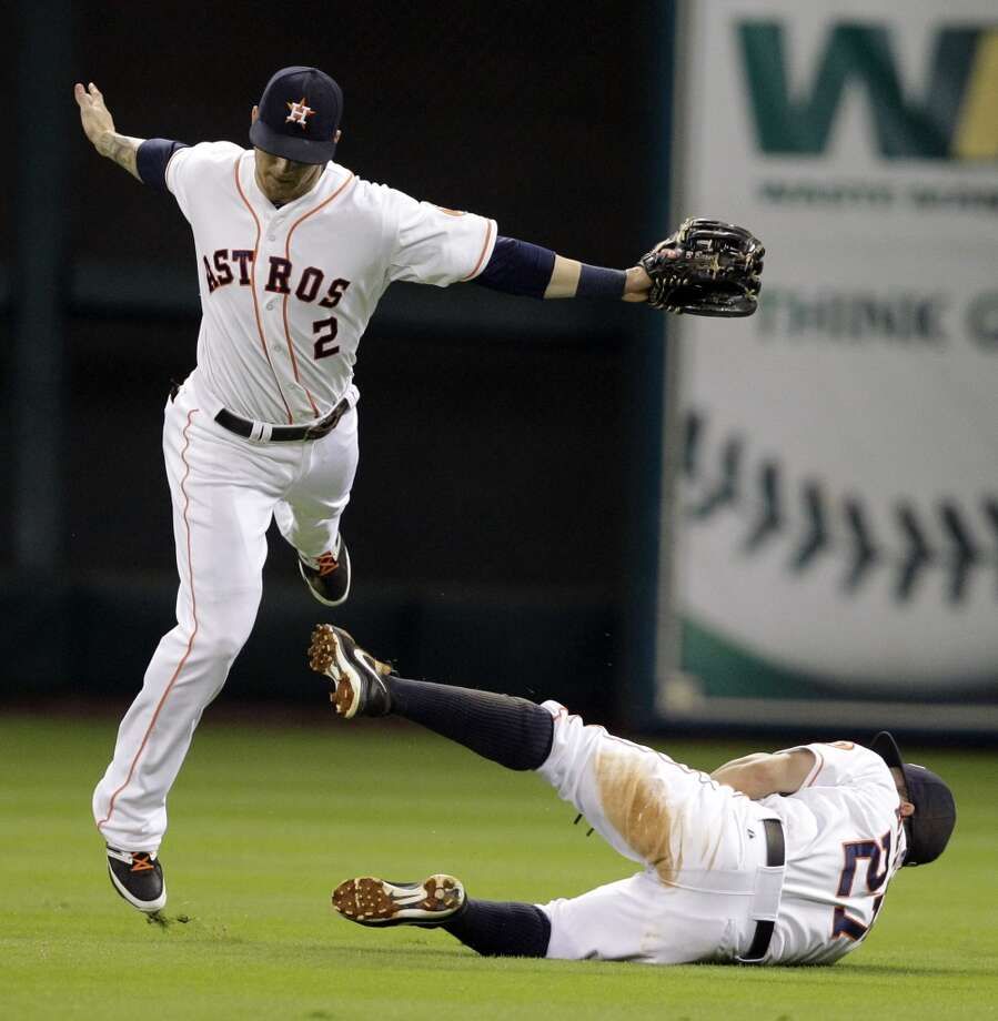 Astros second baseman Jose Altuve ventured out to center field to make an out, causing outfielder Brandon Barnes to hurdle Altuve. Photo: Melissa Phillip, Houston Chronicle