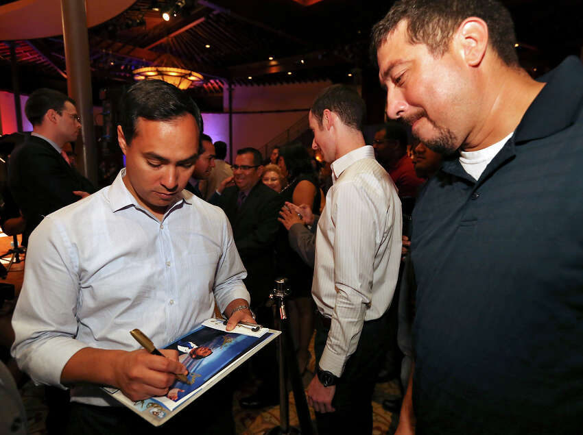 U.S. Rep. Joaquín Castro, D-San Antonio, autographs a photo for Paul Jacobs during the twins 39th birthday celebration held Monday Sept. 16, 2013 at the Pearl Stable.