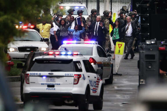 Washington Navy Yard workers file out of a building with their hands up after a shooting rampage that left 13 dead Monday.