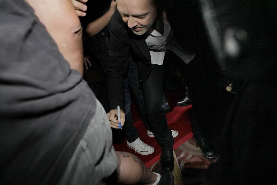 "Metallica drummer Lars Ulrich signs the calf of fan Dave Silva as the band attends the premiere of its Imax 3-D concert film, ""Metallica: Through the Never,"" at the AMC Metreon 16. Photo: Carlos Avila Gonzalez, The Chronicle"