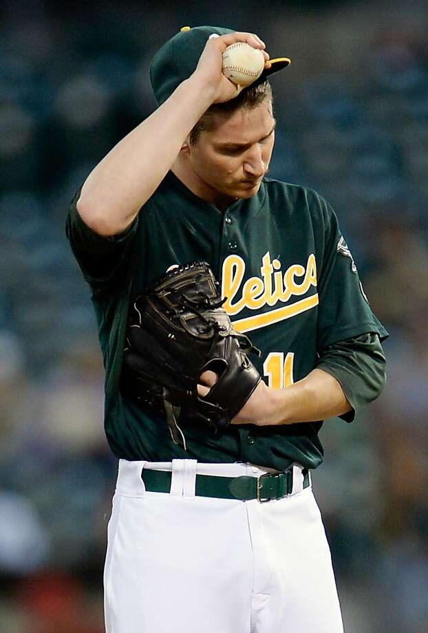 OAKLAND, CA - SEPTEMBER 16:  Pitcher Jarrod Parker #11 of the Oakland Athletics stands on the mound adjusting his cap after giving up his second run to the Los Angeles Angels of Anaheim during the top of the first inning at O.co Coliseum on September 16, 2013 in Oakland, California.  (Photo by Thearon W. Henderson/Getty Images) Photo: Thearon W. Henderson, Getty Images