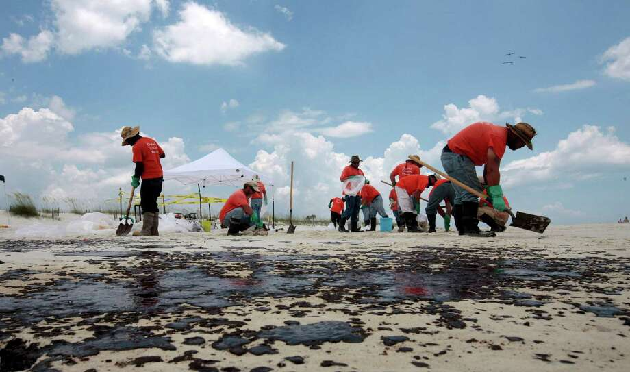 Workers hired by BP pick up oil on the beach in Gulf Shores, Ala., in July 2010. More than 170,000 people worked in some capacity to clean up the spill. Photo: Dave Martin, STF / AP