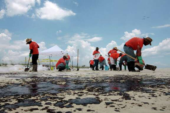 Workers hired by BP pick up oil on the beach in Gulf Shores, Ala., in July 2010. More than 170,000 people worked in some capacity to clean up the spill.