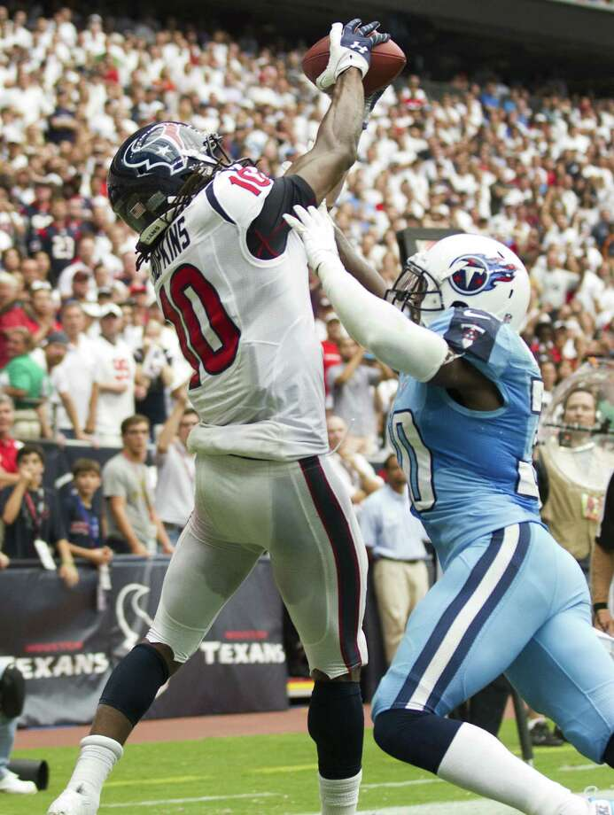 Texans receiver DeAndre Hopkins (left), catching the winning 3-yard TD pass in OT despite the efforts of the Titans' Jason McCourty, had 117 yards receiving in Sunday's game. Photo: Brett Coomer / Houston Chronicle