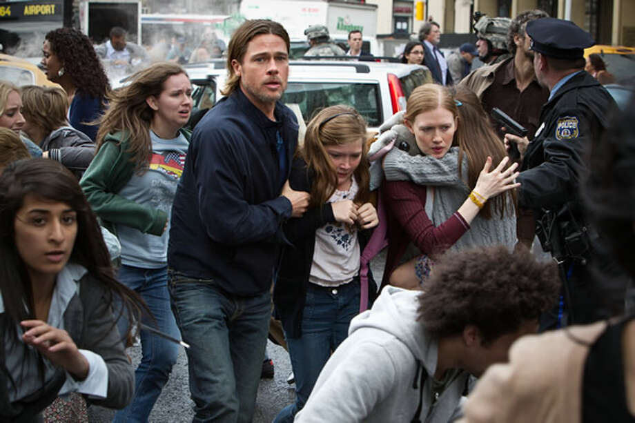 Brad Pitt as Gerry Lane and Mireille Enos as Karin Lane lead their children away from the attacking zombie hordes. Photo: Paramount, 2013