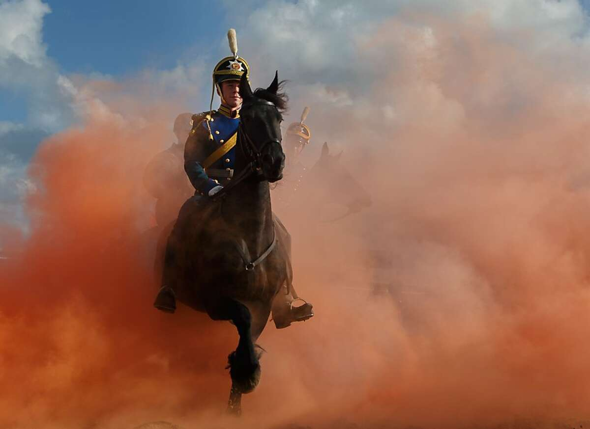 SCHEVENINGEN, NETHERLANDS - SEPTEMBER 16: Horsemen ride their horses through colored smoke during a practice session at the beach of Scheveningen on September 16, 2013 in Scheveningen, Netherlands. Some eighty members of the Dutch cavalry practiced for any possible emergency during tomorrow's Prinsjesdag ceremony which marks the opening of the Dutch parliament. (Photo by Jasper Juinen/Getty Images) *** BESTPIX ***