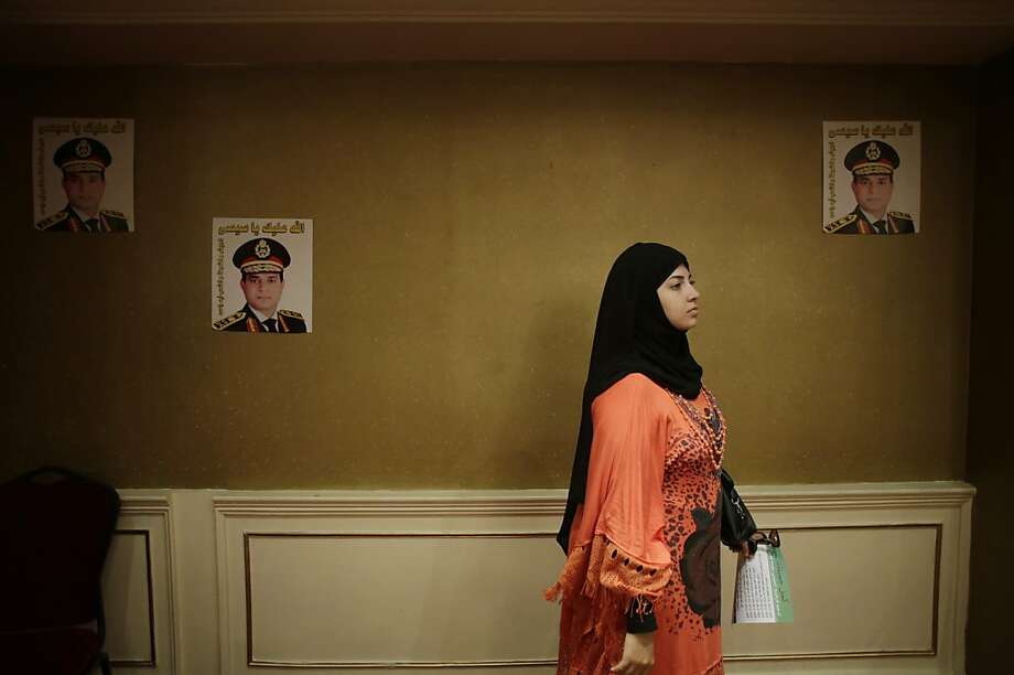 """An Egyptian woman holds a petition form to nominate Defense Minister Gen. Abdel-Fattah el-Sissi to run for president while listening to a talk in a campaign at a hotel in Cairo, Egypt, Monday, Sept. 16, 2013. Posters of Defense Minister el-Sissi are taped on the wall. The Arabic on the posters reads, """"God bless you, Sissi,"""" and """"Army, police and all Egyptians, One arm."""" A group of Egyptian professionals, lawyers and ex-army officers have launched a campaign to collect signatures urging the country's military chief to run for president, just two months after he ousted the first elected leader. (AP Photo/Hiro Komae) Photo: Hiro Komae, Associated Press"""