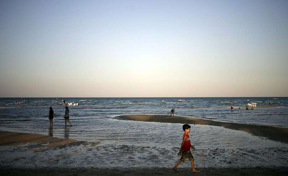 People enjoy a summer day on the beach at Ain El-Sokhna resort on the Red Sea, about 137 kilometers (85 miles) west of Cairo, Egypt, Monday Sept. 16, 2013. (AP Photo/Khalil Hamra) Photo: Khalil Hamra, Associated Press