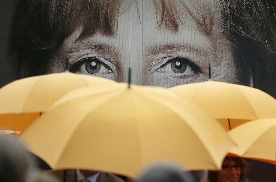 Supporters of the Christian Democratic Union (CDU) hold umbrellas in front of a giant portrait of German Chancellor Angela Merkel during an election campaign event in front of the party's headquarter in Berlin, Germany, Monday, Sept. 16, 2013. (AP Photo/Michael Sohn) Photo: Michael Sohn, Associated Press