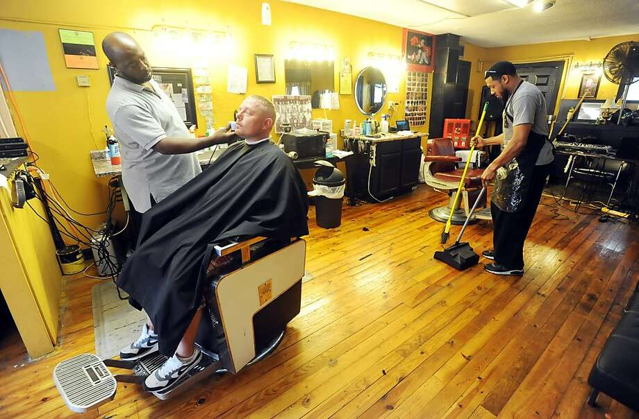 "Jermaine Johnson trims Tripp Harris' beard while Bryson Samuels sweeps hair around his chair Monday Sept. 16, 2013, at A Touch of Class barber shop at 1621 W. Ninth St. in Owensboro, Ky. ""I come here once a week,"" Harris said. The shop offers a straight edge shave. ""Blood runs away from our blades,"" Samuels said. Johnson said they are open seven days a week. (AP Photo/The Messenger-Inquirer, John Dunham) Photo: John Dunham, Associated Press"