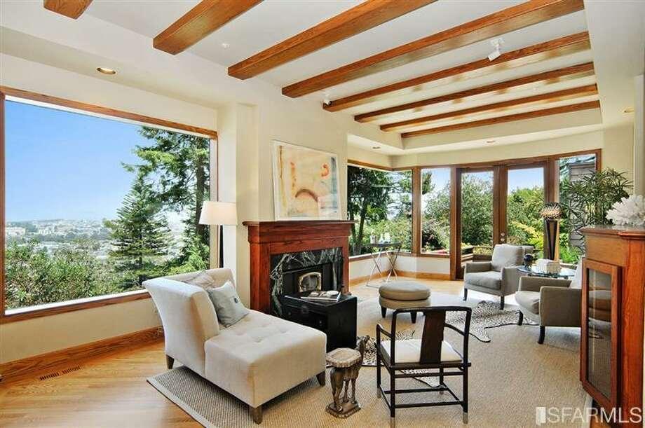 Beamed living room. Photos via MLS/Craig Adams, Coldwell Banker Res. R.E. Svcs