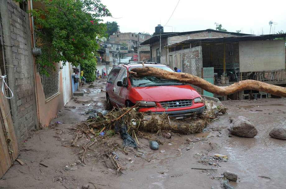 A damaged vehicle stands in the middle of a road after a landslide caused by heavy rains came down on a low income neighborhood in the city of Chilpancingo, Mexico, Monday Sept. 16, 2013.  Tropical Storm Ingrid and remnants of Tropical Storm Manuel drench Mexico's Gulf and Pacific coasts, flooding towns and cities in a national emergency that federal authorities say has caused at least 34 deaths. (AP Photo/Alejandrino Gonzalez) Photo: Alejandrino Gonzalez, STR / AP