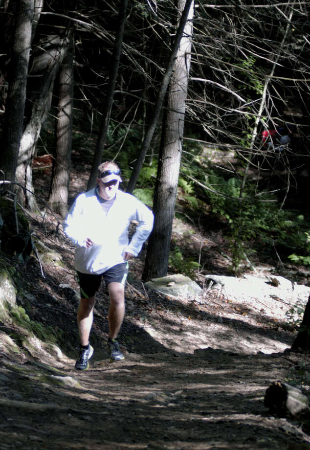 After spending hours prepping a Steep Rock Reservation trail for his runners, New Milford High School girls' cross country coach Giles Vaughan gives it a test run before sending his Green Wave athletes on a rigorous workout in Washington. September 2013 Photo: Norm Cummings