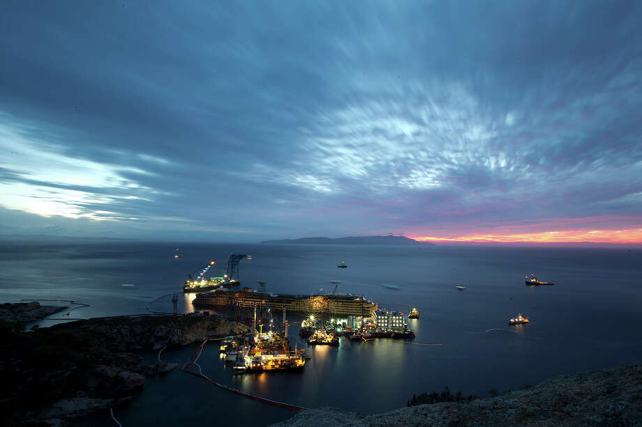 """The Costa Concordia is seen after it was lifted upright on the Tuscan Island of Giglio, Italy, early Tuesday morning, Sept. 17, 2013. The crippled cruise ship was pulled completely upright early Tuesday after a complicated, 19-hour operation to wrench it from its side where it capsized last year off Tuscany, with officials declaring it a """"perfect"""" end to a daring and unprecedented engineering feat. Photo: Andrew Medichini, ASSOCIATED PRESS / AP2013"""