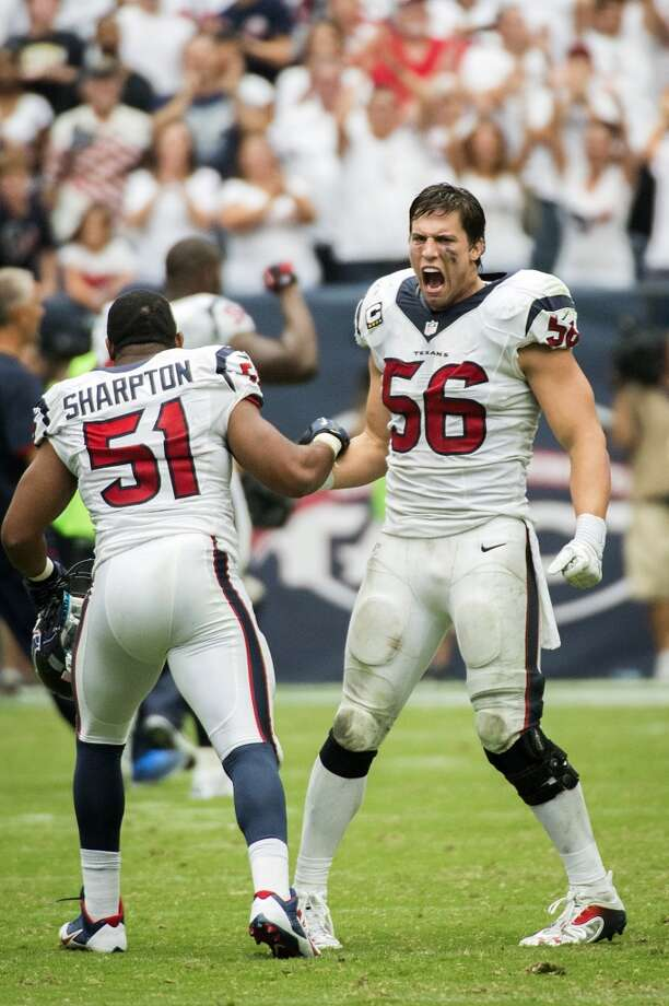 Brian Cushing (56) celebrates with fellow linebacker Darryl Sharpton after a replay review upheld a game-winning 3-yard touchdown catch by wide receiver DeAndre Hopkins during overtime. Photo: Smiley N. Pool, Houston Chronicle