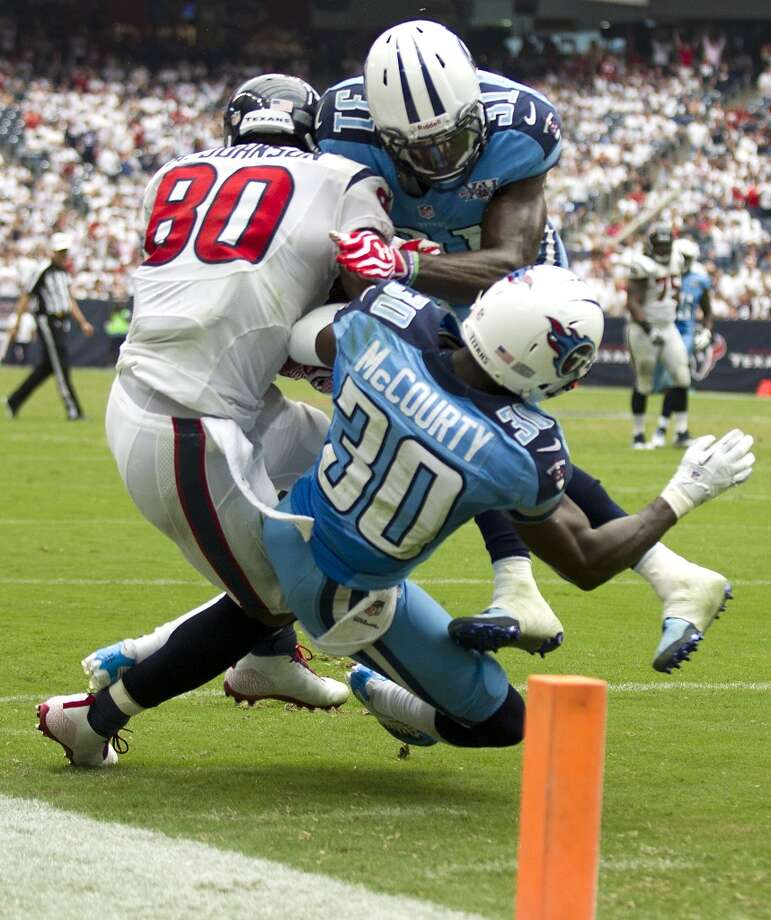 Wide receiver Andre Johnson is hit by Titans strong safety Bernard Pollard and cornerback Jason McCourty (30) as he makes a catch near the goal line late in the fourth quarter. Photo: Brett Coomer, Houston Chronicle