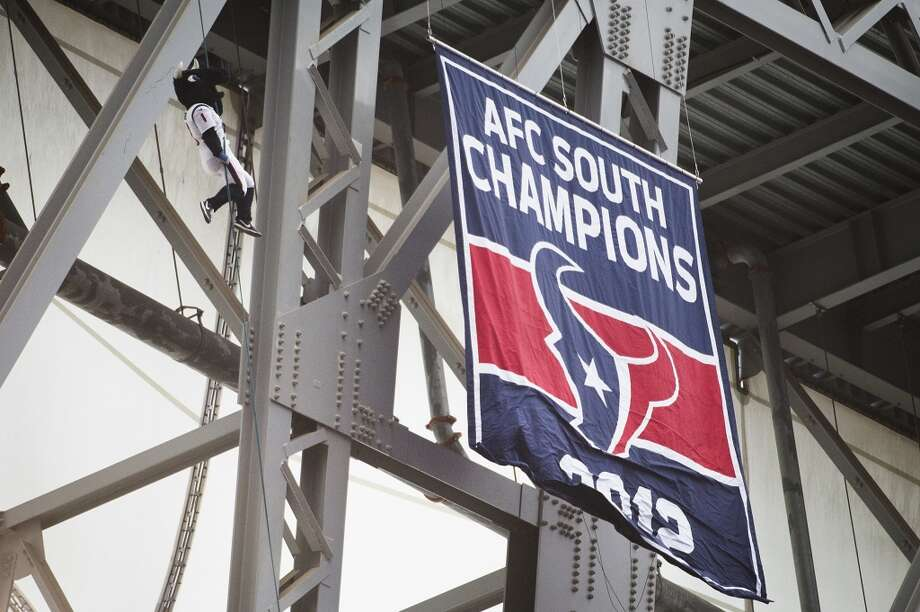 Texans mascot Toro rappels from the top of the stadium as the 2012 AFC South Champions banner is unfurled before facing the Titans. Photo: Smiley N. Pool, Houston Chronicle