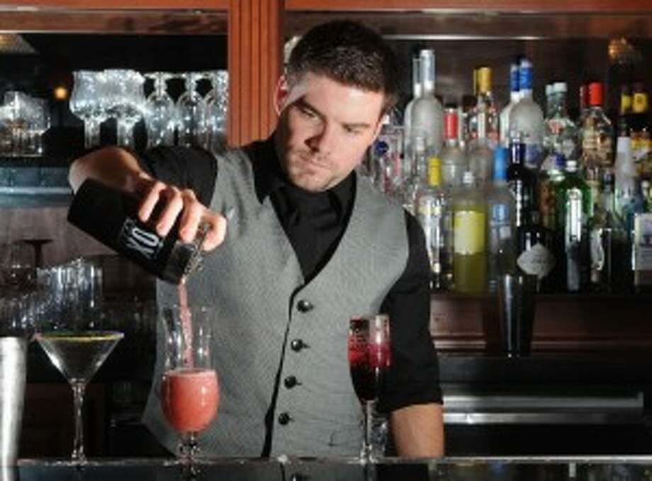 Bartender Max Keen pours a drink at Suga's.> > Questions we still have from the '90s
