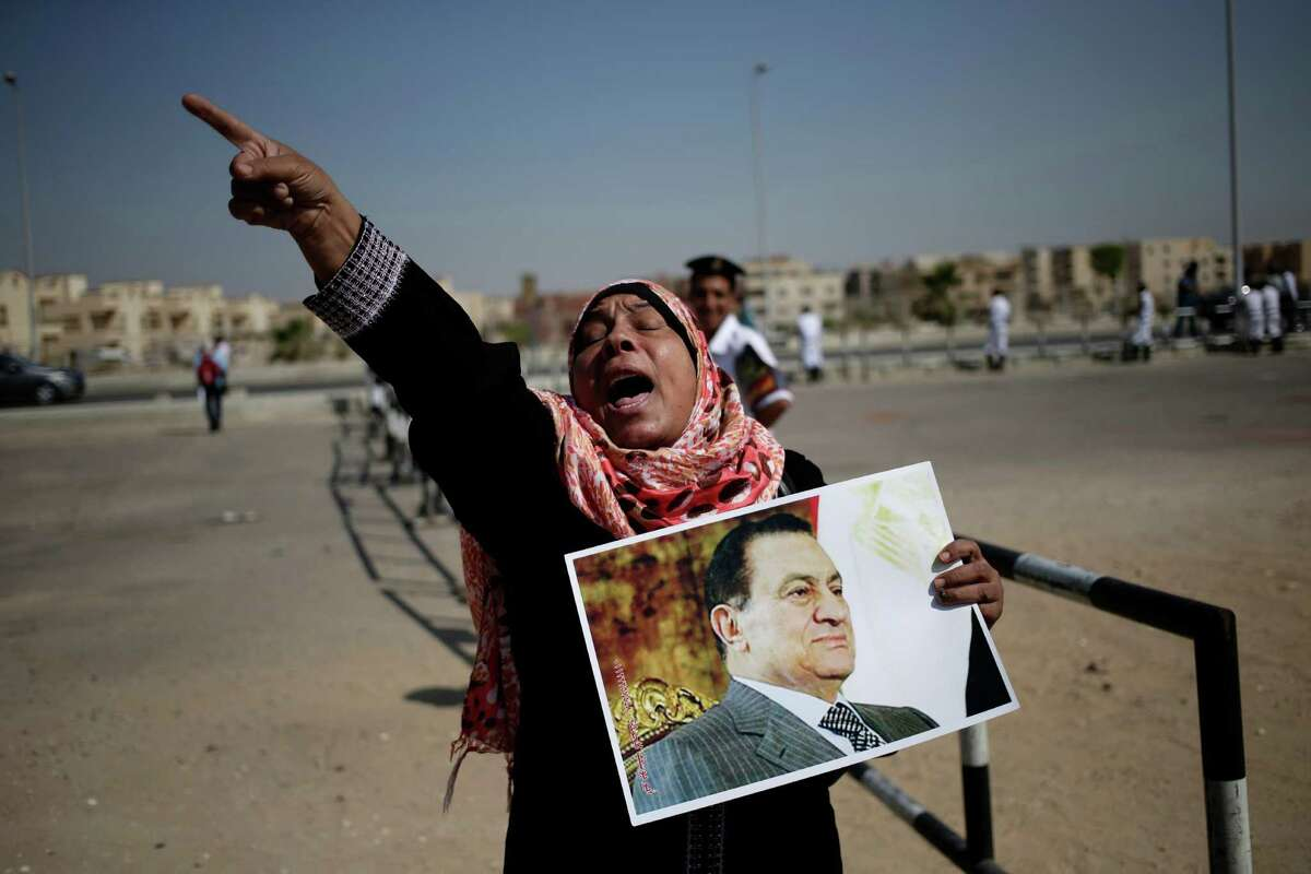 An Egyptian woman carrying a photo of ousted president Hosni Mubarak chants slogans against ousted President Mohammed Morsi and the Muslim Brotherhood as she expresses her support for Mubarak at a court in Cairo, Egypt, Saturday, Sept. 14, 2013. The ousted long-time autocrat went back in court as his trial resumed on charges related to the killings of some 900 protesters during the 2011 uprising that led to his ouster.