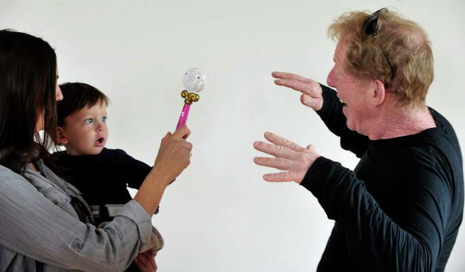 """Alan Obsatz, right, reacts to his grandson, Gus, 1, waving a magic wand, as author Jane Collins, creator of the Enjella series about a tooth fairy turned """"Elbow Fairy,"""" presents an interactive program for kids at Tilly Foster Farm, in Brewster, N.Y. Saturday, Sept. 14, 2013. Photo: Michael Duffy / The News-Times"""