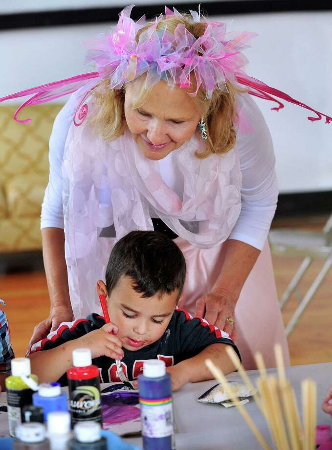 "Author Jane Collins, creator of the Enjella series about a tooth fairy turned ""Elbow Fairy,"" helps Matthew Farbman, 4, make wings, during an interactive program for kids at Tilly Foster Farm, in Brewster, N.Y. Saturday, Sept. 14, 2013. Photo: Michael Duffy / The News-Times"