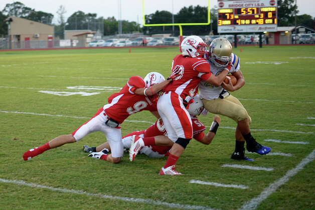 Kelly's Sean Bebeau, 23, tries to keep in bounds while several Cardinals try to pull him down at Bridge City Stadium Friday night. Photo provided by Drew Loker. Photo: Drew Loker / ©2013. www.drewloker.com