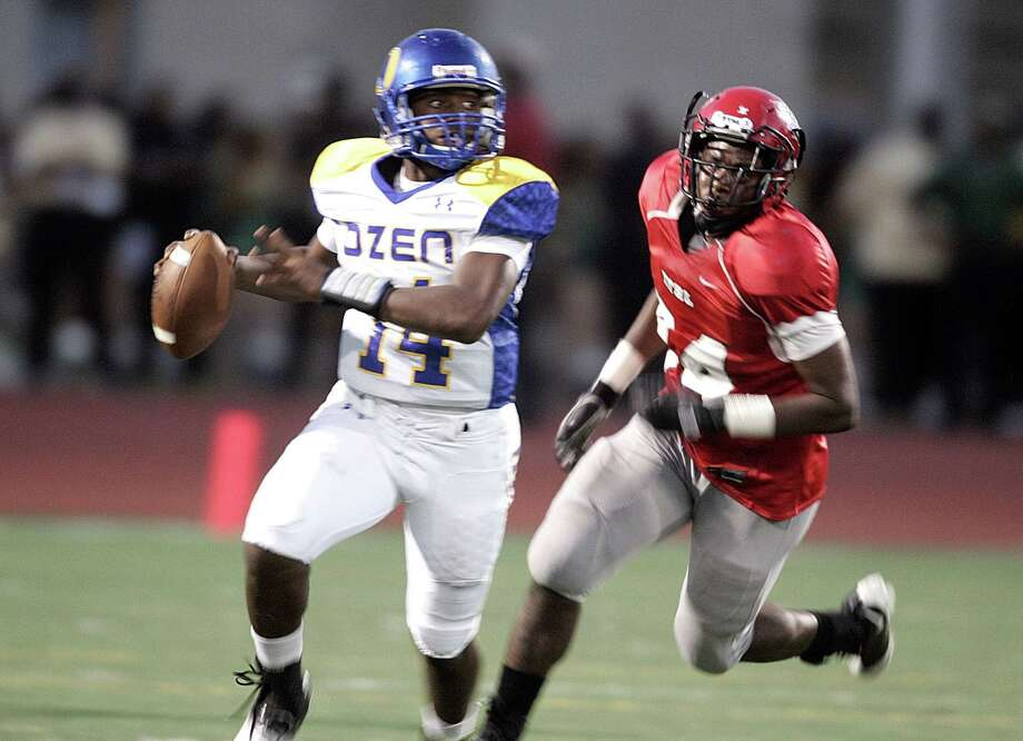 Ozen quarterback Joshua Boyd (14) looks for a receiver with Cedar Hill defensive end Jaylin Penton (74) on his heels as Ozen played Cedar Hill in high school football at the Lone Star Classic at Dallas John E. Kincaide Stadium Saturday afternoon September 14, 2013. Cedar Hill defeated Ozen 48-0. (Special to the Beaumont Enterprise Bob Booth) Photo: Bob Booth, Stringer / Bob Booth