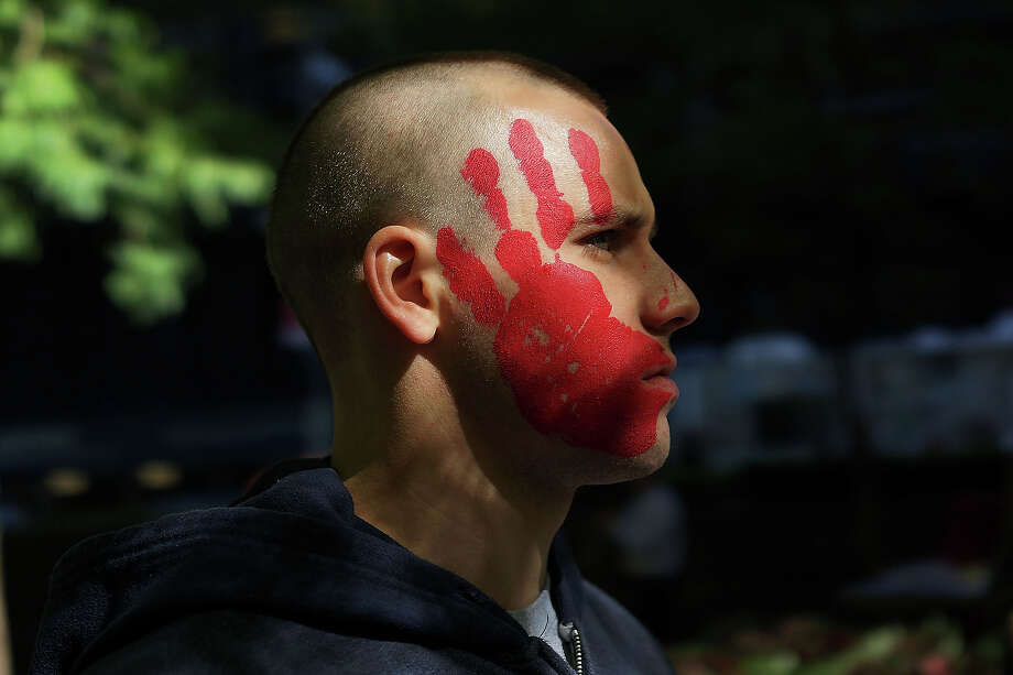 A protester affiliated with Occupy Wall Street demonstrates at Zuccotti Park near the New York Stock Exchange on the second anniversary of the movement on September 17, 2013 in New York City. Numerous rallies and events across the city were planned for the movement which takes aim at inequality and financial greed and which has influenced activist moments around the world. While police presence was high in New York, with a helicopter flying above the park, no incidents had been reported by the afternoon. Photo: Spencer Platt, Getty Images / 2013 Getty Images