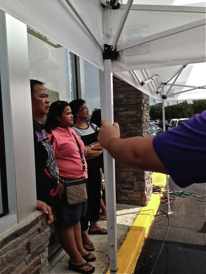 The line snakes around the corner and under a temporary awning on Sept 16, 2013 at the new Jollibee Filipino fast food. Photo: Alison Cook