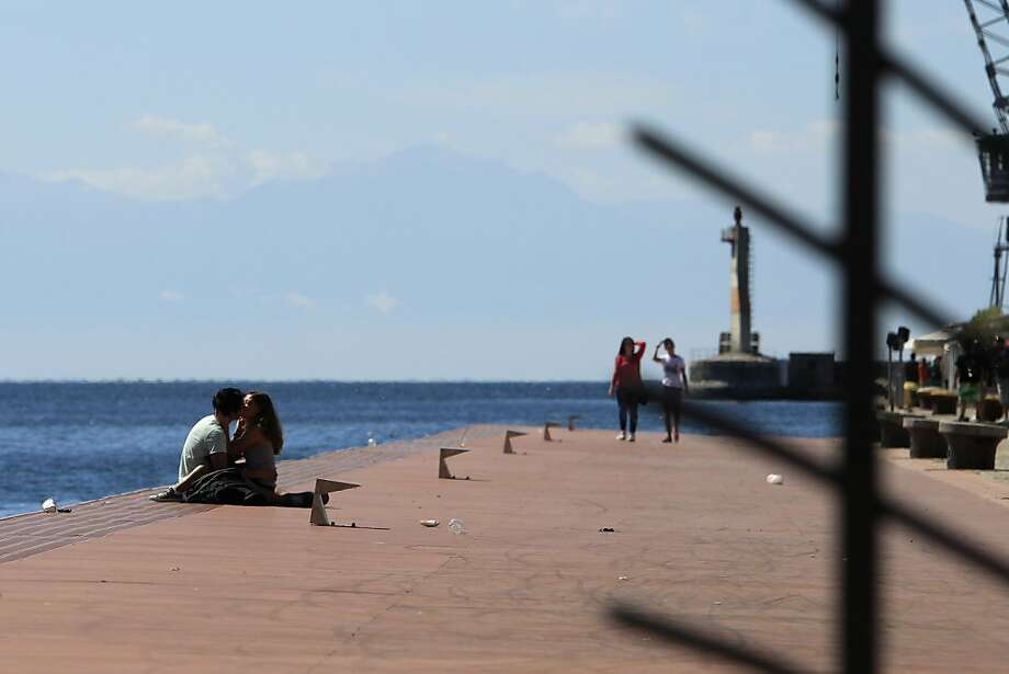 Kissing on the dock o' the bay: A young couple get romantic in the northern port city of Thessaloniki, Greece. Photo: Nikolas Giakoumidis, Associated Press