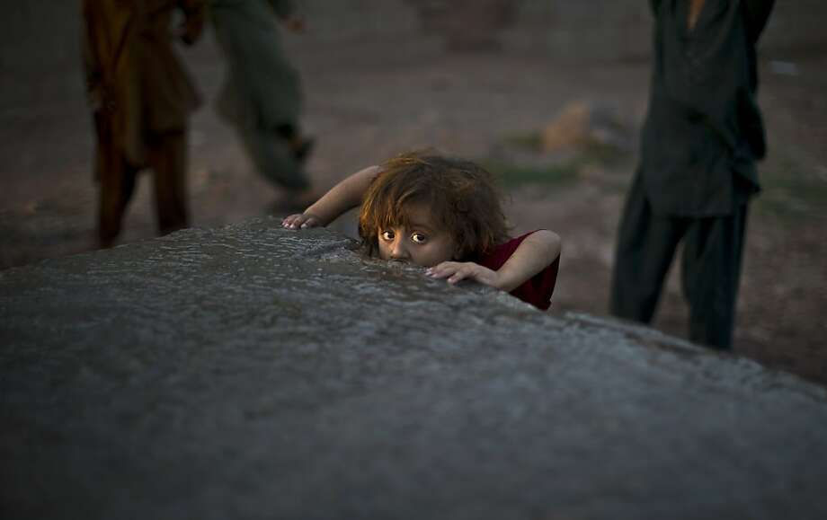 A refugee girl drinks water leaking from a public water source on the outskirts of Islamabad. Pakistan 