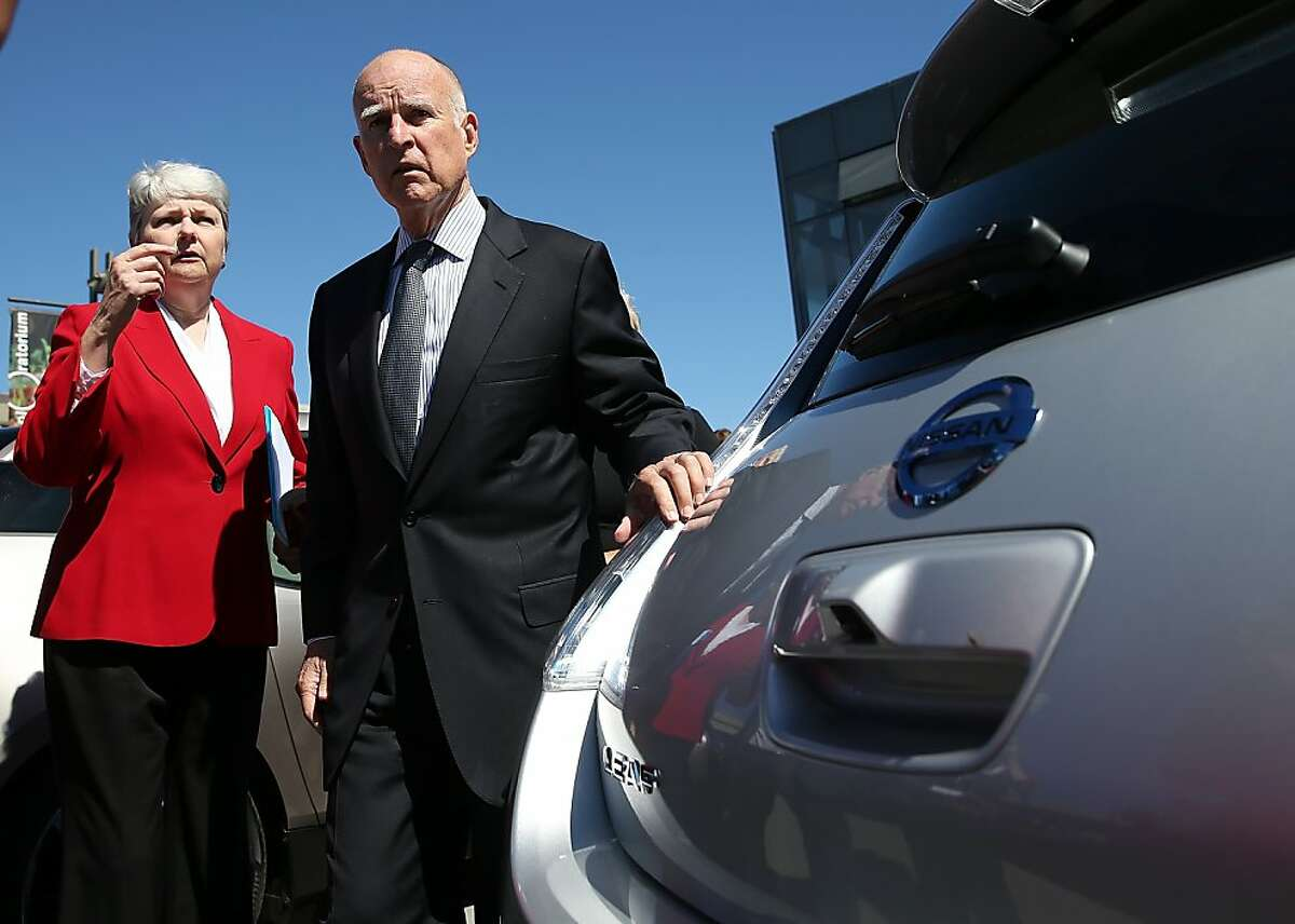 In this file photo, California Gov. Jerry Brown (right) and California Plug-in Electric Vehicle Collaborative executive director Christine Kehoe (left) look at a dsiplay of electric cars during the Drive The Dream event at the Exploratorium in San Francisco.
