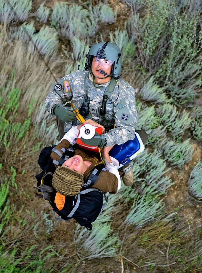 National Guard to the rescue:Staff Sgt. Jose Pantoja, a flight medic with the Colorado Air National Guard, rides with an unidentified evacuee 