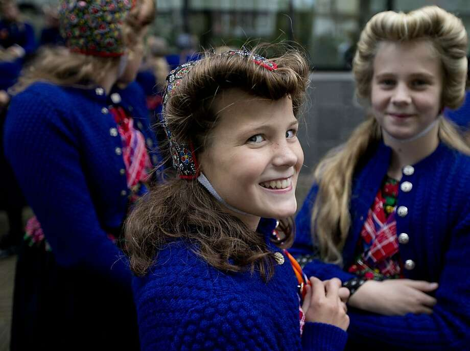 Lasses of the lowlands:Sophie Feijer and other girls are dressed in traditional attire as they celebrate the opening of the Dutch parliament at The Hague. Photo: Peter Dejong, Associated Press