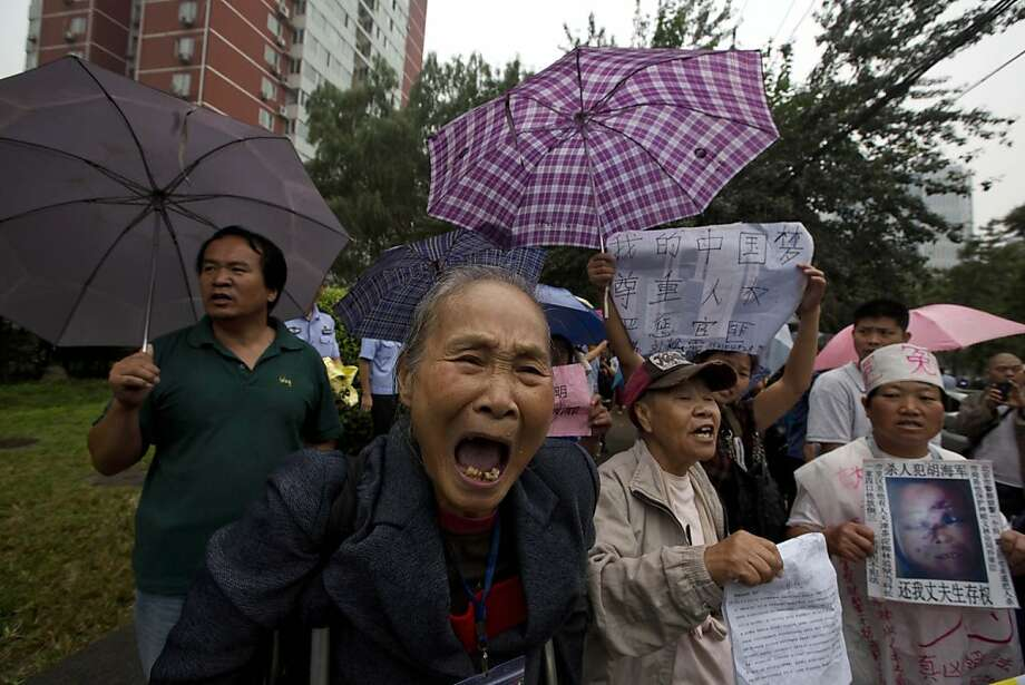 Petitioners with their own grievances shout support for Ji Zhongxing who is on trial for endangering public safety by setting off an explosion two months ago at Beijing's airport, outside a courthouse in Beijing, China, Tuesday, Sept. 17, 2013. The explosion which only injured Ji himself drew wide condemnation but also sympathy from many observers who saw his act as a sign that the country does not adequately address grievances of increasingly marginalized members of its society. (AP Photo/Ng Han Guan) Photo: Ng Han Guan, Associated Press