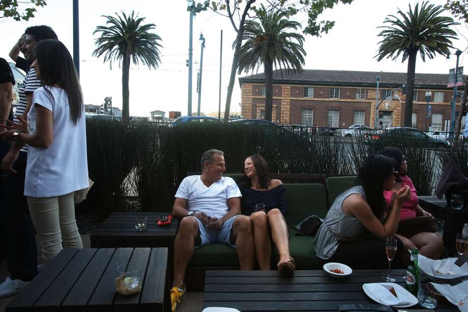 Rob Elliott and Tia Hartley (left) drove in from Walnut Creek to hang out at Americano on the west side of the Embarcadero in San Francisco. Photo: Liz Hafalia, The Chronicle