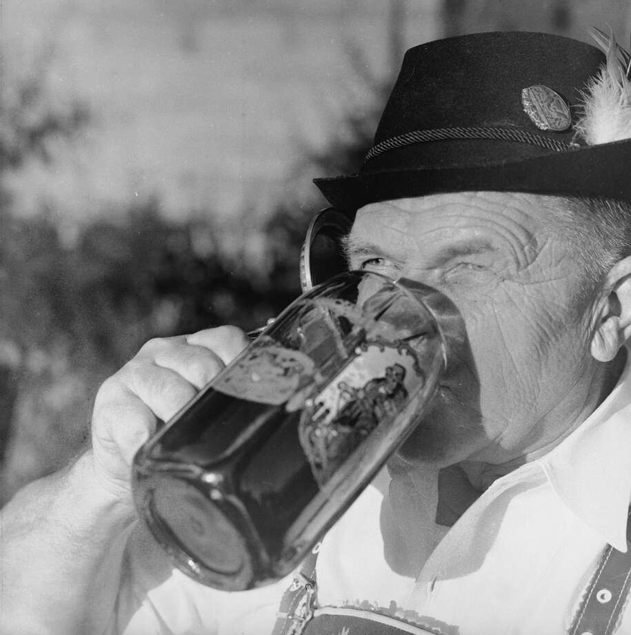 A man wearing a Tyrolean hat drinks a stein of beer at an American equivalent of the German Oktoberfest. Photo: Dennis Rowe, Getty Images / Hulton Archive