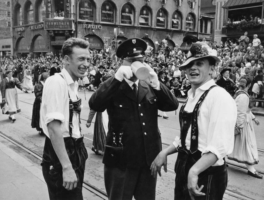 A policeman is happy to join two Bavarians in a mug of German beer during the Oktoberfest celebrations in Munich, Germany, 24th September 1958. Photo: FPG, Getty Images / 2012 Getty Images