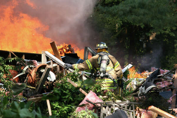 A firefighter battles a blaze after a propane tank exploded destroying a house at 305 Webbs Hill Road in North Stamford Tuesday afternoon.
