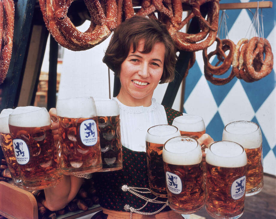 A 1975 portrait of a waitress holding ten mugs of beer in her hands near hanging displays of soft pretzels at an Oktoberfest celebration. Photo: Hulton Archive, Getty Images / Archive Photos