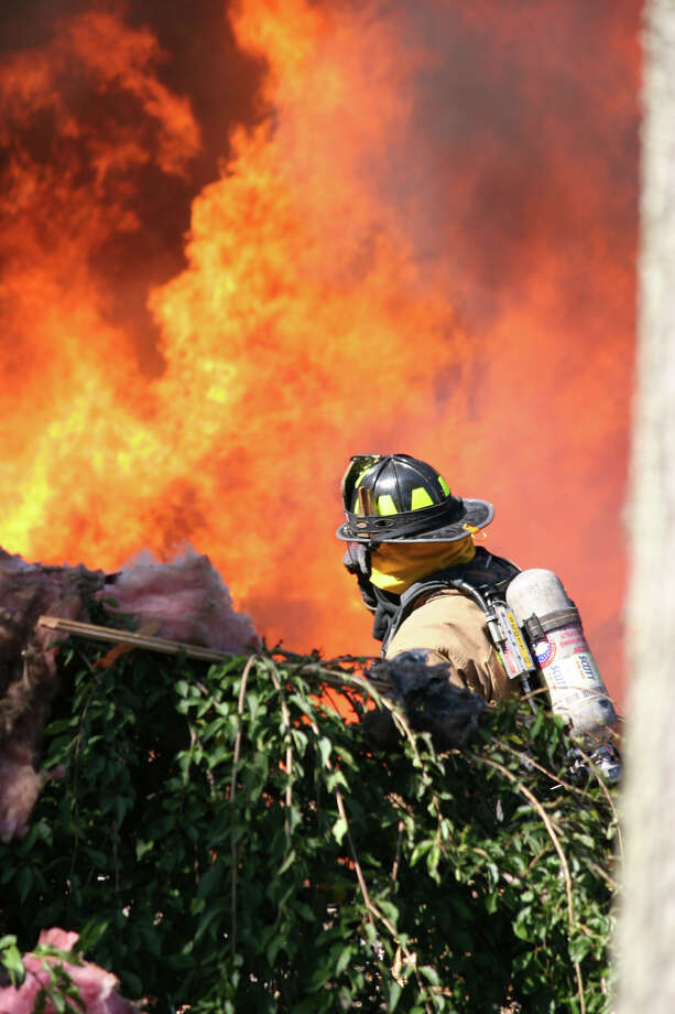 A firefighter battles a blaze after a propane tank exploded destroying a house at 305 Webbs Hill Road in North Stamford. Photo: Bill Tenca