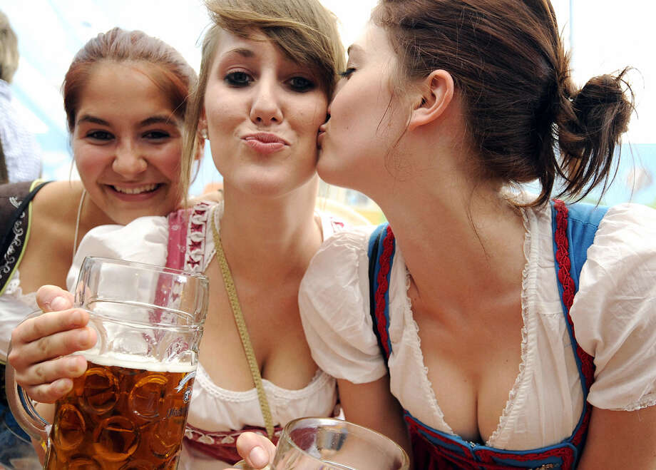 Young women in dirndl dresses pose with beer mugs at the Oktoberfest beer festival on Sept. 19, 2009. Photo: OLIVER LANG, Getty Images / 2009 AFP