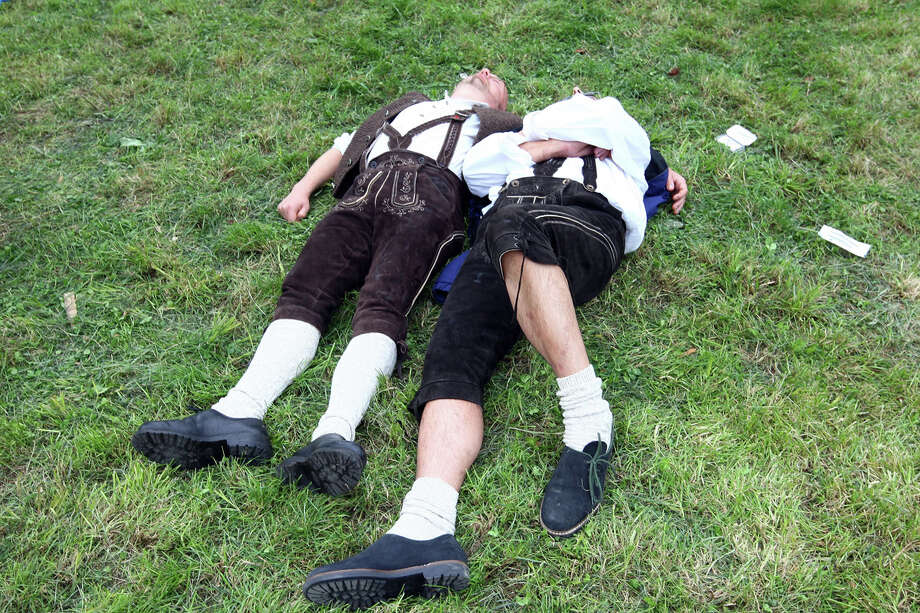 Two Bavarian dressed men sleep on the ground during Oktoberfest beer festival on Sept. 21, 2008 in Munich, Germany. Photo: Johannes Simon, Getty Images / 2008 Getty Images