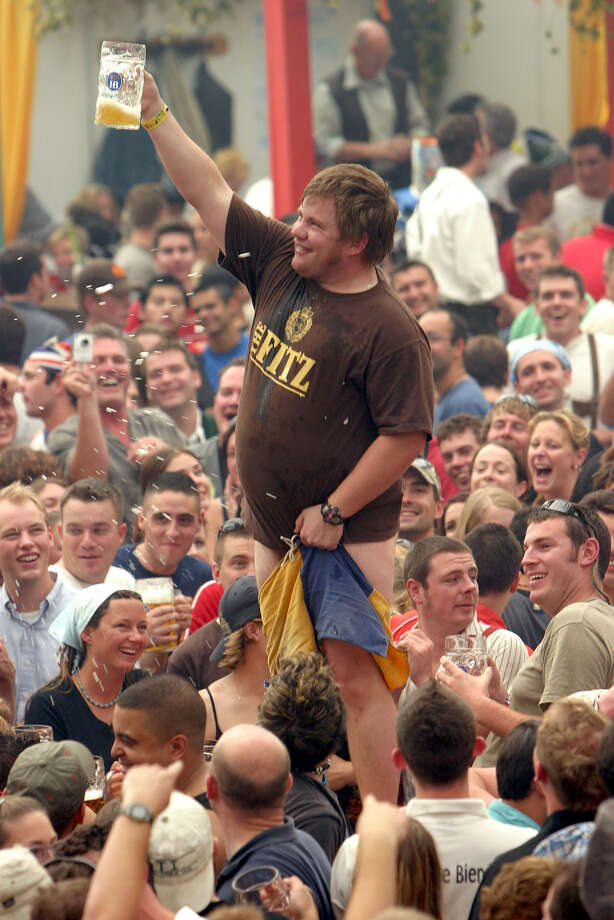 "A reveler holds onto his pants after downing his one liter mug of beer in an area known as ""the pit"" at the Hofbraeuhaus tent on the opening day of the 2004 Oktoberfest Sept. 18, 2004 in Munich, Germany. Photo: Sean Gallup, Getty Images / 2004 Getty Images"