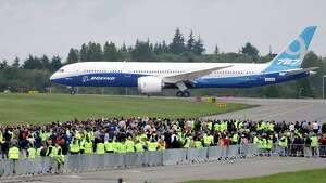 A Boeing 787-9 rolls past employees and guests before taking off  Tuesday, Sept. 17, 2013, at Paine Field in Everett, Wash. The 787-9 is 20 feet longer and can seat 40 more passengers than the original 787-8, which carries between 210 and 250 passengers. The new version of the Dreamliner also can carry more cargo and fly farther.